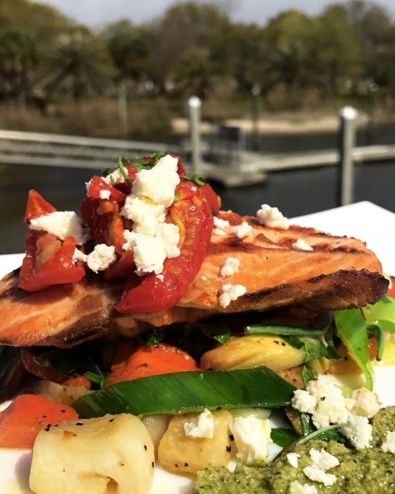 Try our daily special! Grilled salmon over sautéed roasted root veggies, served with broccoli walnut pesto, and finished with fresh feta cheese and marinated tomatoes. #fishhousepensacola #downtownpensacola #upsideofflorida
