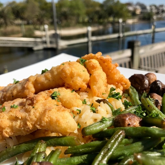 Treat yourself to lunch today! Our Fish House special is fried grouper over cheesy rice served with sautéed green beans and mushrooms and finished with tangy meunière sauce and crispy sweet potato hay. #fishhousepensacola #downtownpensacola #upsideofflorida